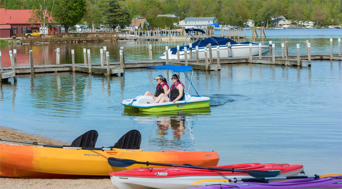 Guests enjoying the lake with the town of Center Harbor in the background.